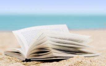 Foto di un libro sulla sabbia