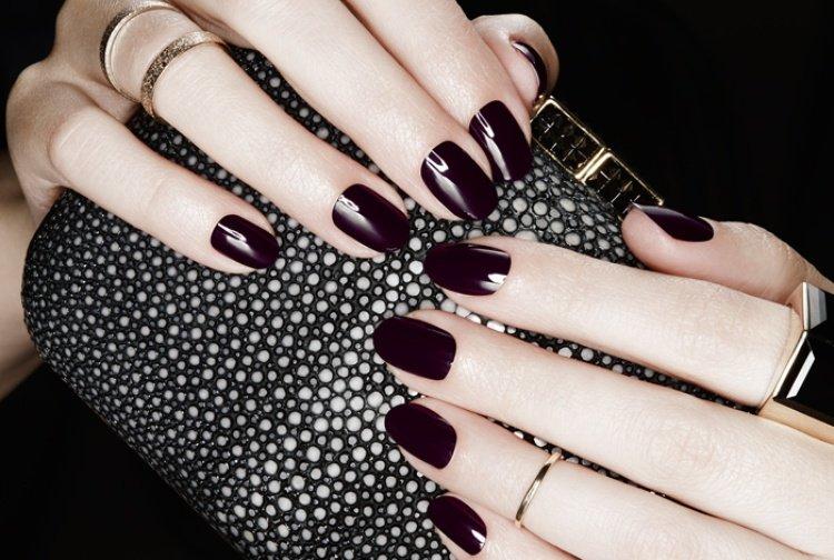 Foto di mani con smalto scuro che stringono una borsa