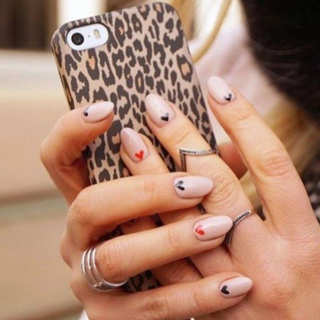 Foto di nail art con smalto rosa e piccoli cuori disegnati