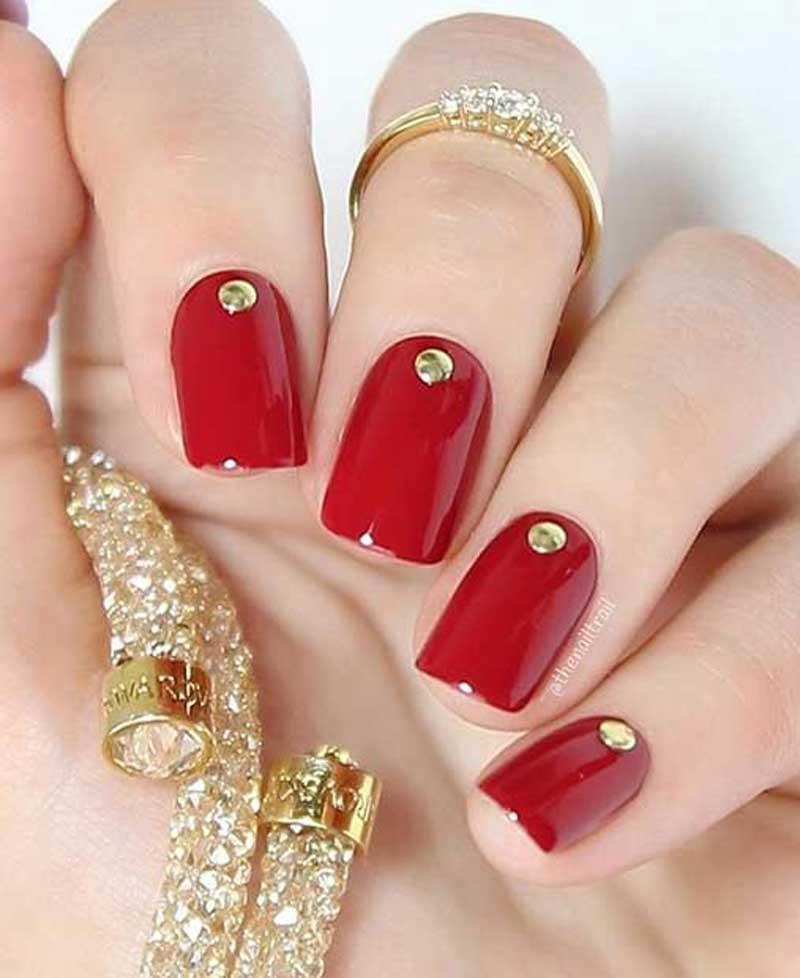 Foto di unghie rosse con decorazioni oro