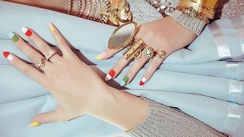 Foto di mani con diversi smalti colorati