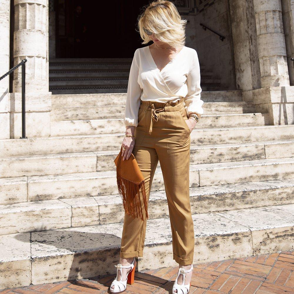 Foto di look primavera estate 2019: camicia bianca di seta e pantaloni beige